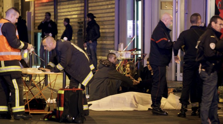 ATTENTION EDITORS - VISUAL COVERAGE OF SCENES OF INJURY OR DEATH  A general view of the scene that shows rescue services personnel working near the covered bodies outside a restaurant following a shooting incident in Paris, France, November 13, 2015.   REUTERS/Philippe Wojazer - RTS6VON