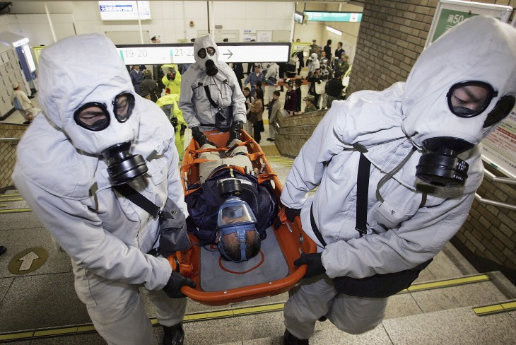 SAITAMA, JAPAN - NOVEMBER 17: Men in chemical protection suits carry an injured person during a joint anti-terrorism drill conducted by Japan Ground Self-Defense Force, Police and Fire Department at Onomiya Station on November 17, 2005 in Saitama City, Saitama Prefecture, North of Tokyo, Japan. The drill conducted amid increased terrorism concerns was based on the scenario of a sarin nerve gas attack at a station. (Photo by Junko Kimura/Getty Images)