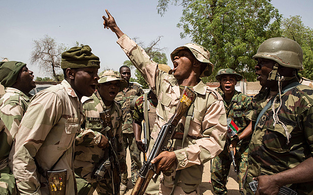 TOPSHOTS Nigerian troops celebrate after taking over Bama from Boko Haram on March 25, 2015. Nigeria's military has retaken the northeastern town of Bama from Boko Haram, but signs of mass killings carried out by Boko Haram earlier this year remain.  AFP PHOTO / NICHOLE SOBECKINichole Sobecki/AFP/Getty Images